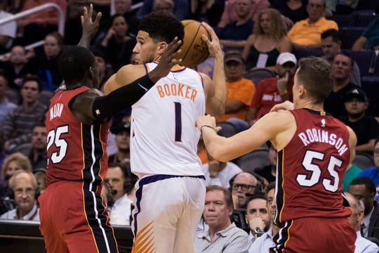 Phoenix Suns' Devin Booker (1) looks to pass as he is double-teamed by Miami Heat's Kendrick Dunn (25) and Duncan Robinson (55) during the second half of an NBA basketball game Thursday, Nov. 7, 2019, in Phoenix. (AP Photo/Darryl Webb)