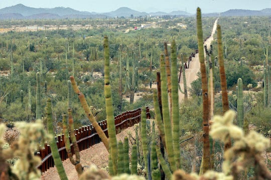 This Feb. 17, 2006 photo, shows a fence separating Organ Pipe Cactus National Monument, right, and Sonoyta, Mexico, running through Lukeville, Ariz. Activists say the 30-foot barrier will block wildlife migration, destroy sacred sites and imperil endangered species.