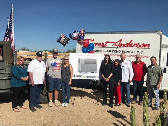 Dan and Brenda Dennison pose with loved ones after winning a free air conditioning unit from Forrest Anderson.