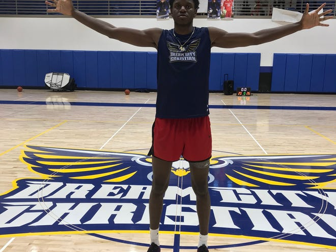 Dream City Christian guard/forward Alex Tchikou shows off his long wingspan in the team's basketball gym.