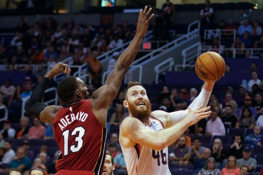 Phoenix Suns' Aron Baynes (46) shoots next to Miami Heat's Bam Adebayo (13) during the second half of an NBA basketball game Thursday, Nov. 7, 2019, in Phoenix. (AP Photo/Darryl Webb)