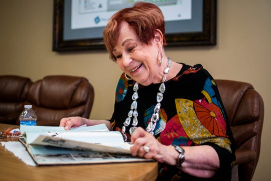 Charlotte Dodie Gussie-Richmond, who served for two years in the Navy as a disbursing clerk during the Korean War, smiles as she looks through her 1954 U.S. Navy training book for Company 25 in Bainbridge, Maryland at Fellowship Square senior living facility in Mesa on Nov. 7, 2019.