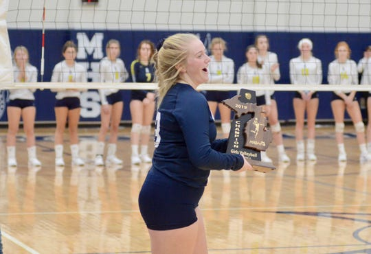 Marysville's Joeleen Gaffney accepts the championship trophy against Algonac during the Division 2 volleyball district final on Thursday, Nov. 7, 2019.