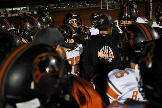 Members of the Almont football team huddle before their Division 5 district final against Marine City on Friday, Nov. 8, 2019.