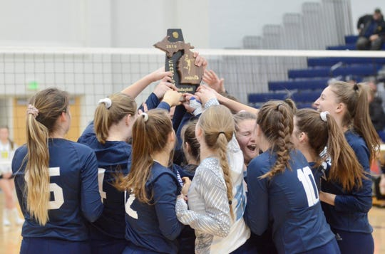 The Marysville volleyball team celebrates with the Division 2 district championship trophy on Thursday, Nov. 7, 2019.