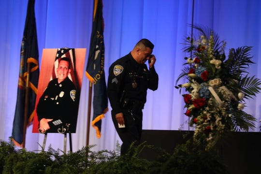 Rochester Police Sgt. Henry Rivera walks off stage after finishing his eulogy for Officer Manny Rivera