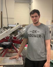 Sage Genovese, a Gen Z staffer at Crazy Dog T-shirts in Rochester, models the OK Boomer shirt.
