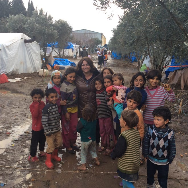 Ilge Karancak- Splane takes a group photo with the children at the refugee camp.