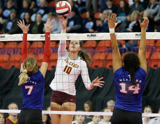 Luxemburg-Casco's Holly Baierl (10) tips the ball over Wisconsin Lutheran's Grace Schneider (7) and Bria Wigley (14) on Friday at the WIAA state volleyball tournament at the Resch Center in Ashwaubenon.