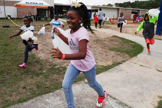 Oak Ridge Elementary School second grader Sa'Maree Williams runs towards the bounce houses and face painting tent as the school celebrates its 50th anniversary Friday, Nov. 8, 2019.
