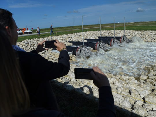 Spectators watch as water pumped from the C-44 canal begins to flow into cell 2 of the C-44 Reservoir and Stormwater Treatment Area following the ceremonial start triggered by Florida Gov. Ron DeSantis on Friday, Nov. 8, 2019, in western Martin County.