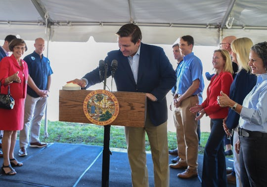 Florida Gov. Ron DeSantis presses the ceremonial button to begin the flow of water pumped from the C-44 Canal into cell 2 of the new C-44 Reservoir Stormwater Treatment Area on Friday, Nov. 8, 2019, as Florida Sen. Gayle Harrell (left), and Jacqui Thurlow-Lippisch (far right), governing board member of the South Florida Water Management District, cheer him on. The new stormwater treatment area, located in western Martin County near the Indiantown Airport, is a major component of the Indian River Lagoon-South Restoration Project to improve the health of the Indian River Lagoon and the St. Lucie River.