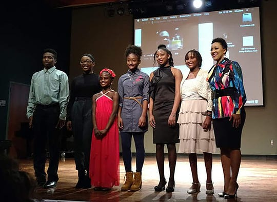 Brittney Brackett, right, organizer of the Outstanding Youth Awards Initiative, stands on stage with the winners of the 2018 Outstanding Youth Awards