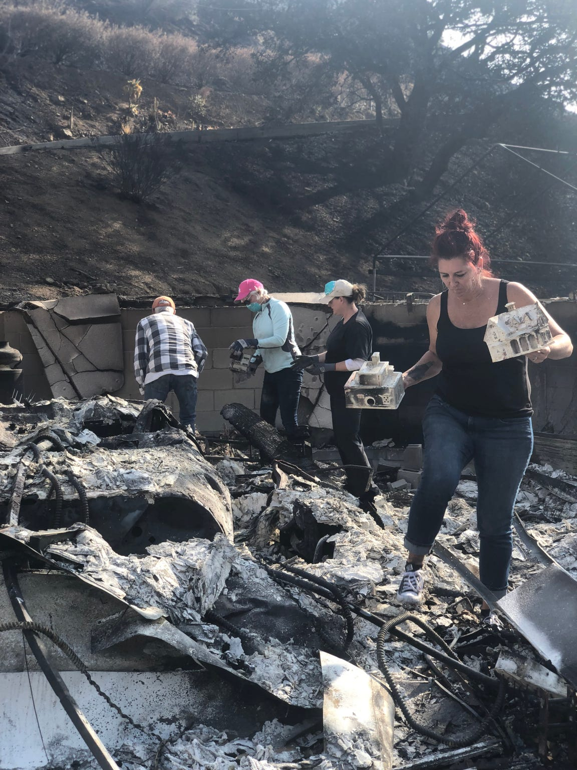 Members of the Koch family sift through the ashes of the former family home on Yellow Hill Road after the Woolsey Fire swept through the area in November 2018.