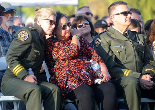 Members of the Ventura County Sheriff's Office comfort Karen Helus on Thursday at Conejo Creek Park North in Thousand Oaks, where a memorial to Borderline shooting victims was unveiled. Helus' husband, Sgt. Ron Helus, was among those killed.