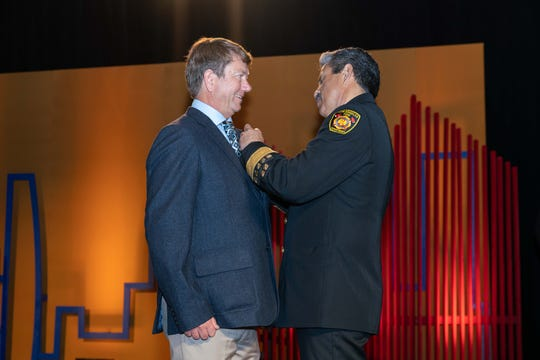 From left, retired pilot Dave Nordquist receives a Medal of Merit from Los Angeles Fire Chief Ralph Terrazas.