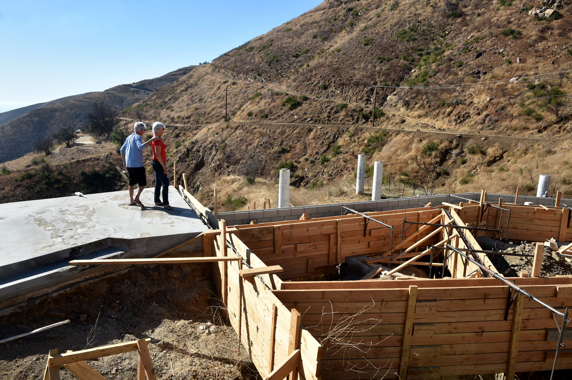 Larry Koch and his wife, Pam Davison, visit their property on Yellow Hill Road in the Santa Monica Mountains. Their home was leveled by the Woolsey Fire a year ago, in November 2018.