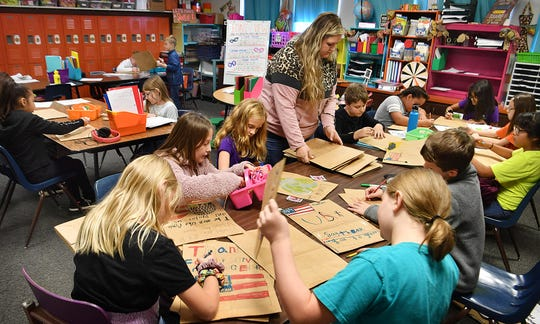 Ben Franklin Elementary fourth graders decorate grocery sacks with pictures and poems. The sacks will be used at the Sheppard Air Force Base commissary to bag groceries of local veterans.