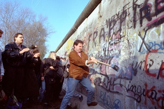 An unidentified West Berliner swings a sledgehammer, trying to destroy the Berlin Wall near Potsdamer Platz, on November 12, 1989, where a new passage was opened nearby.