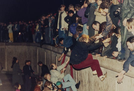 East Berliners get helping hands from West Berliners as they climb the Berlin Wall that divided the city near the Brandenburger Tor on November 10, 1989. The citizens facing the West celebrate the opening of the wall that was announced by the East German Communist government hours before.