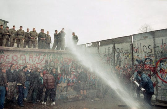East German border guards use a hose to discourage West Berliners near Brandenburg gate, in Berlin on Nov. 11, 1989. The citizens from the west tried to demolish the wall, demanding it be pulled down.
