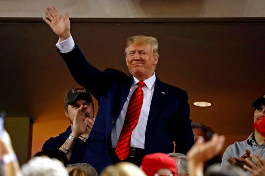 President Donald Trump waves to the crowd, which booed him, during Game 5 of the 2019 World Series.