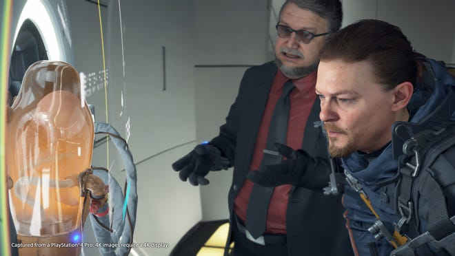 "The characters Deadman (Guillermo del Toro) and Sam Porter Bridges (Norman Reedus) look at BB in a scene from the video game """"Death Stranding."""