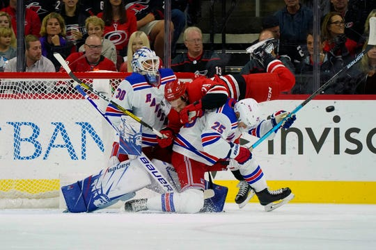 Carolina Hurricanes center Brian Gibbons  is hit by a first period shot against New York Rangers defenseman Libor Hajek, right, and goaltender Henrik Lundqvist at PNC Arena in Raleigh, N.C.