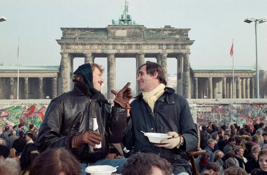 Two Berliners chat in front of Brandenburg Gate in Berlin on Nov. 12, 1989, while having lunch on a visitor's platform near the Berlin Wall.