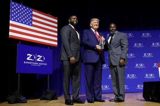 "President Donald Trump is awarded the Bipartisan Justice Award by Matthew Charles, right, one of the first prisoners released by the First Step Act, during the ""2019 Second Step Presidential Justice Forum"" at Benedict College on Oct. 25 in Columbia, S.C."