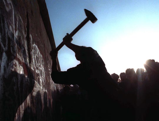 A man hammers away at the Berlin Wall on Nov. 12, 1989, as the border barrier between East and West Germany was torn down after 28 years, symbolically ending the Cold War.