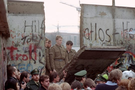 East German border guards are seen through a gap in the Berlin wall after demonstrators pulled down a segment of the wall at Brandenburg gate, Berlin on November 11, 1989.