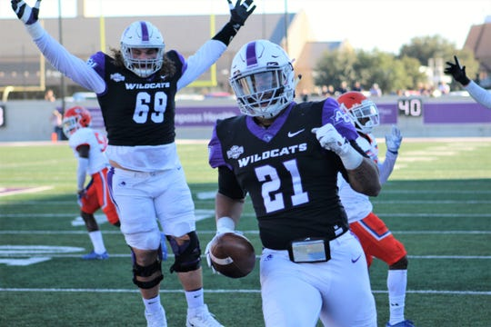 Offensive lineman Kade Parmelly (69), the former Wylie standout, reacts as ACU teammate Tracy James (21) crosses the goal line for a touchdown that gives the Wildcats a 10-0 lead over Sam Houston State on Saturday at Wildcat Stadium.