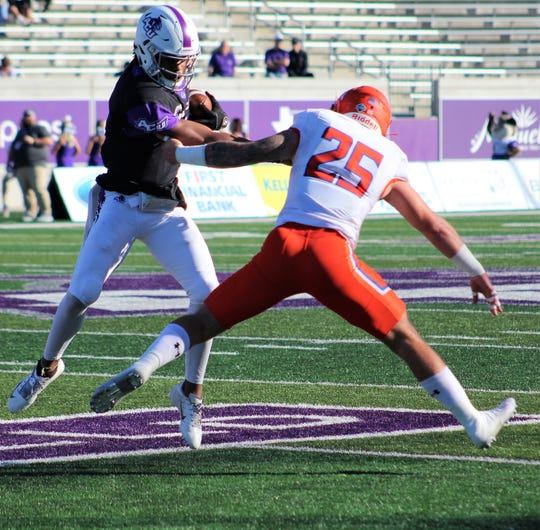 Abilene Christian quarterback Sema'J Davis tries to evade the grasp of Sam Houston defender Hunter Brown (25) on a keeper Saturday at Wildcat Stadium.