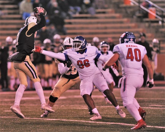 Cooper defensive lineman Douglas Sims (96) tries to pull down Amarillo High quarterback Will Maynard late in the first half of the district title game in Amarilo.
