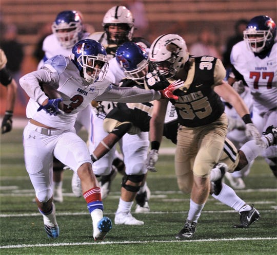 Cooper running back Noah Garcia, left, tries to fend off Amarillo High defender Brock Ewing during a run in the first half. Amarillo High won the District 2-5A Division I game 49-35 Friday at Dick Bivins Stadium in Amarillo.