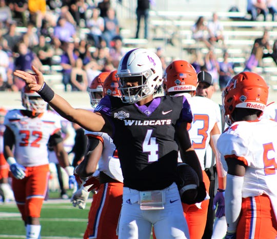 Abilene Christian quarterback Sema'J Davis (4) stands among Sam Houston players to signal first down during the first half of their Southland Conference game Saturday at Wildcat Stadium. Davis's 11 carries were the most of an ACU back, and he completed the one pass he threw.