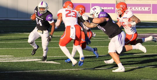 Abilene Christian running back Tyrese White (24) looks for a way to get by Sam Houston defender Tristin McCollum during the first half of Saturday's game at Wildcat Stadium. White had 49 yards rushing to lead his team.