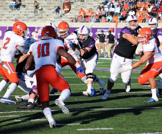 The football pops into the air off an Abilene Christian player and will be intercepted by Sam Houston defender Will Lockett (2) to snuff out a Wildcats drive in the red zone Saturday at Wildcat Stadium.
