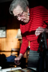 Margaret Swicegood Fort looks at a book containing a photograph of her grandfather in her home in Arden November 6, 2019.