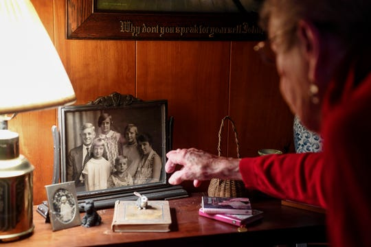 Margaret Swicegood Fort points out a photograph of herself with her brothers, sisters and mother in her home in Arden November 6, 2019.