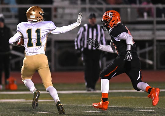 Vestal's Anthony Policare IV looks to stiff-arm Union-Endicott's Samuel Malloy during Friday's Section 4 Class A final at U-E.