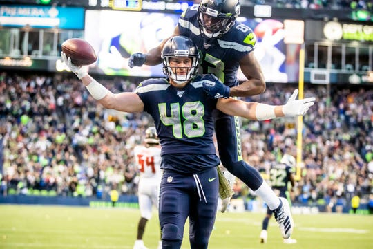 Seahawks tight end Jacob Hollister celebrates after scoring the winning touchdown in overtime with wide receiver David Moore on his back at an NFL football game against the Tampa Bay Buccaneers, Sunday, Nov. 3, 2019, in Seattle.