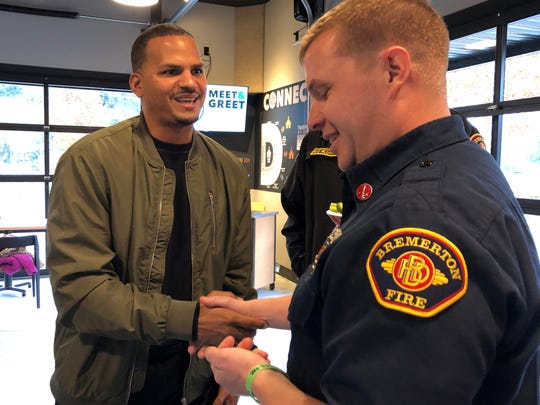 Jeremy McCrimmon, left, gifts Bremerton Firefighter Craig Patti with a keepsake coin. Patti was among the responders who helped bring McCrimmon back to life after 27 minutes without a heartbeat.
