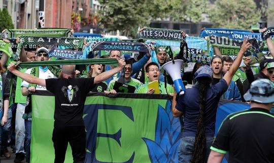 Members of the Emerald City Supporters hold up scarves during the traditional March to the Match. The Sounders set a new standard for how an expansion franchise should operate and the aspirations it should carry. And now they are being rewarded with the crown jewel of hosting the final with the home team playing.