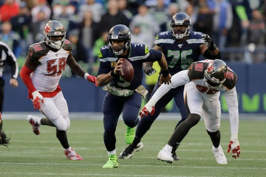 Seattle Seahawks quarterback Russell Wilson (3) scrambles away from Tampa Bay Buccaneers defensive end Jason Pierre-Paul (90) during overtime of an NFL football game, Sunday, Nov. 3, 2019, in Seattle.