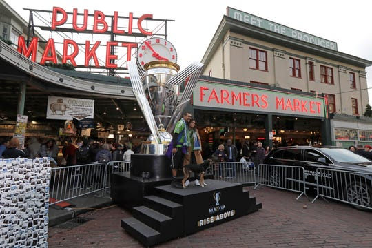 Fans wearing Seattle Sounders gear pose for a photo with a giant replica of the MLS Cup trophy, Friday, Nov. 8, 2019, at Pike Place Market in Seattle. Toronto FC is scheduled to face the Seattle Sounders on Sunday in the MLS Cup soccer match in Seattle, the third time the two teams will have met for the MLS championship.