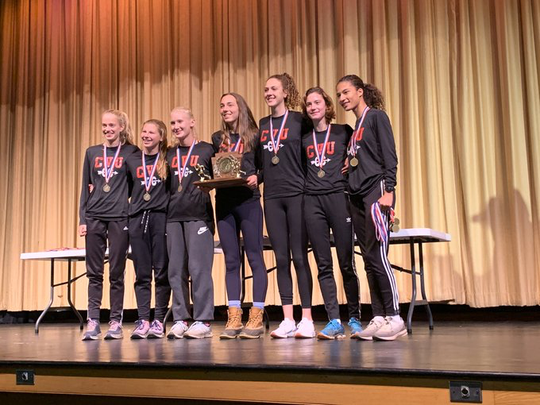 The CVU girls cross-country running team poses with the New England championship trophy on Saturday.