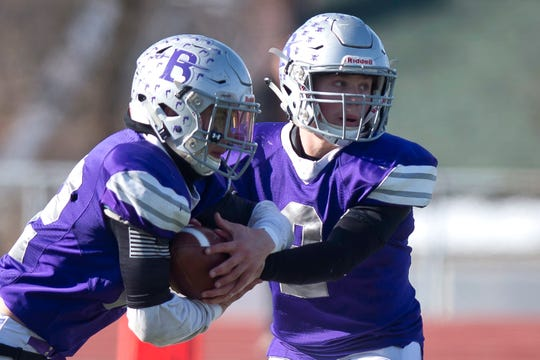Brattleboro's Tyler Millerick, right, reads the option handoff to Chris Frost during the Division II high school football state championship game in Rutland on Saturday, Nov. 9, 2019.