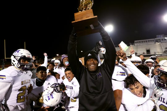 Miller Buc's head coach Justen Evans holds up the district championship trophy following the game against the Moody Trojans at Cabaniss Stadium on Friday, November 8, 2019. The Bucs win put them at 10-0 for the season, which is the first time since 1955 they have been 10-0.